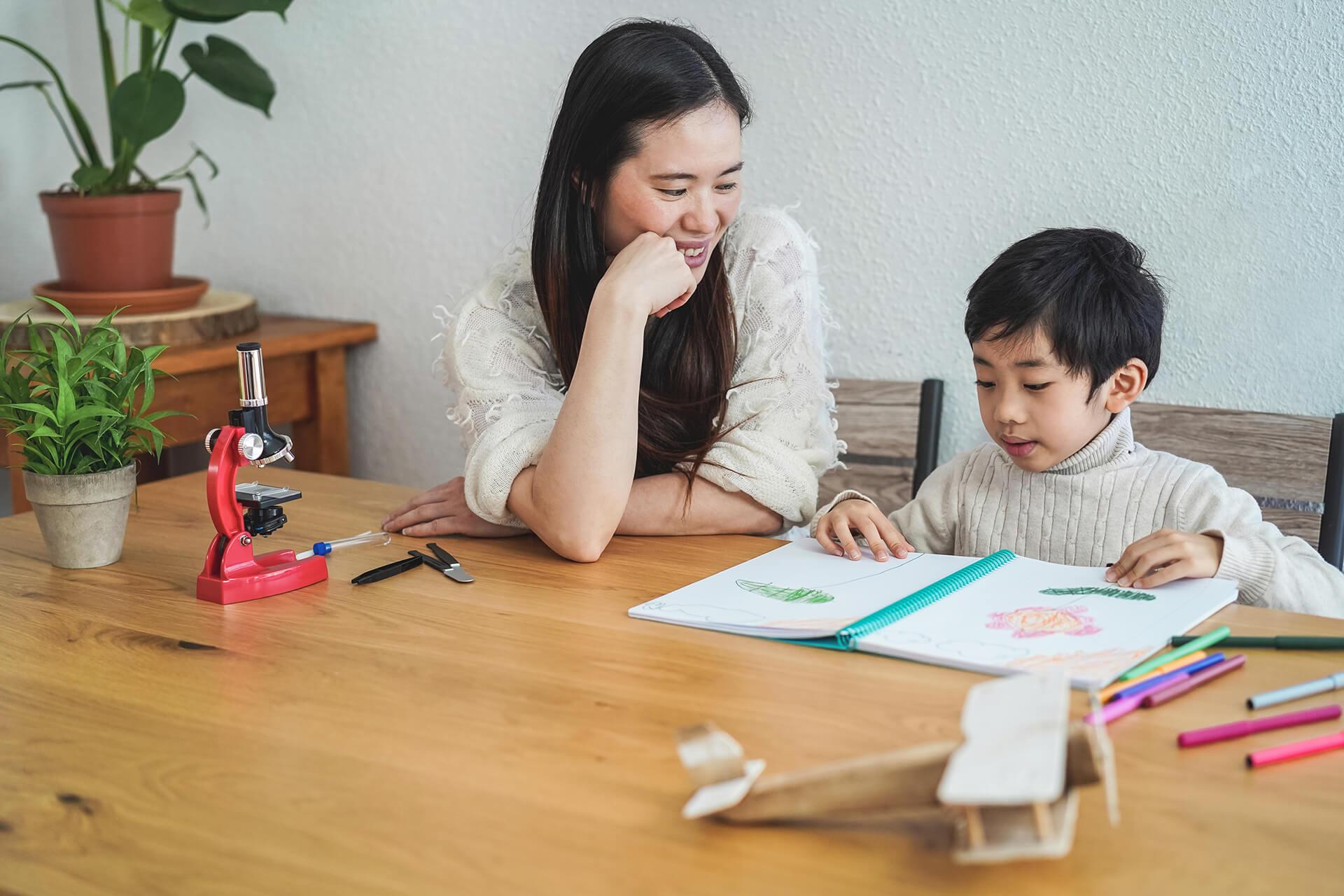 asian-teacher-working-with-child-boy-at-preschool--V84MDR9